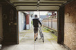 Rear view of man with bicycle walking on footpath seen through garage