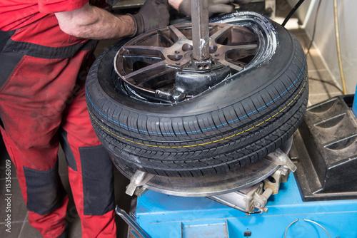 Valokuva  Mann montiert neuen Reifen auf einer Felge in der Werkstatt