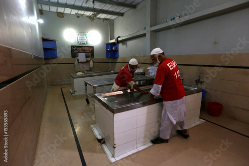 Employees of the Edhi Foundation morgue clean work tables