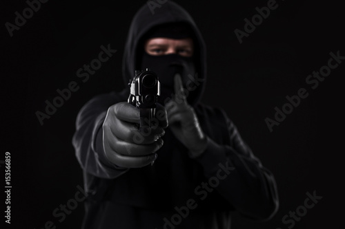 Masked robber with gun aiming into the camera against a black background Fototapet