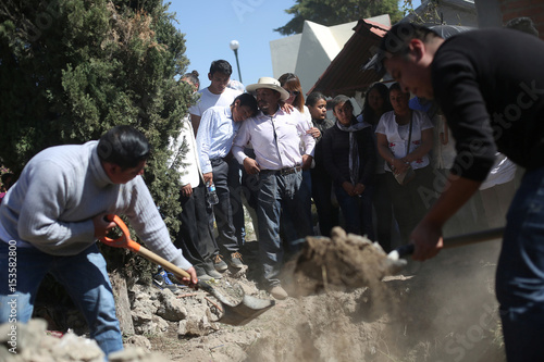 Relatives and friends shovel dirt on the coffin of a victim