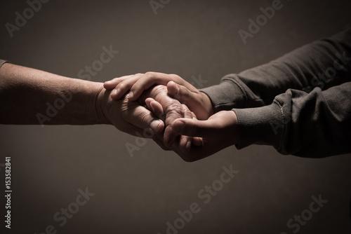 Obraz na płótnie Child hands holding senior woman's hands on brown background