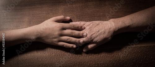 Plakat Dziecko wręcza trzymać starsze kobiet ręki na brown tle