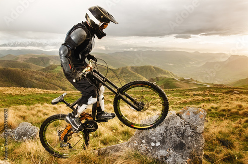 Ryder in full protective equipment on the mtb bike climbs on a rock against the Wallpaper Mural