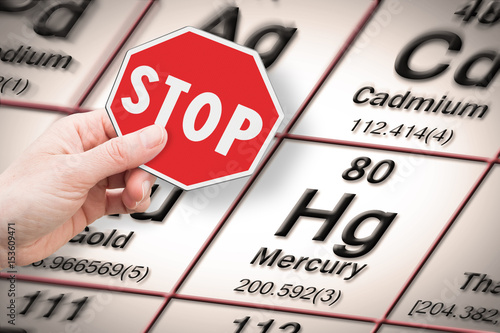 Fotografie, Obraz Stop heavy metals - Concept image with hand holding a stop sign against a mercur