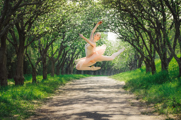 Fototapeta Taniec / Balet Ballerina dancing outdoors and jumping high into the air