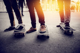 Boys skateboarders Feet in pants and bryaks in frayed sneakers stand on the skateboard. Concept of a team of friends doing sports on the asphalt skateboarding