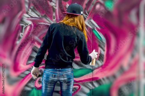 Plakat Młoda miejska dziewczyna rysuje graffiti, współczesna ikoniczna kultura ulicznej młodości. Nowoczesna kultowa ulica kultury miejskiej. Koncepcja nowoczesnego wzornictwa. Graffiti sztuki ulicy. selektywna ostrość