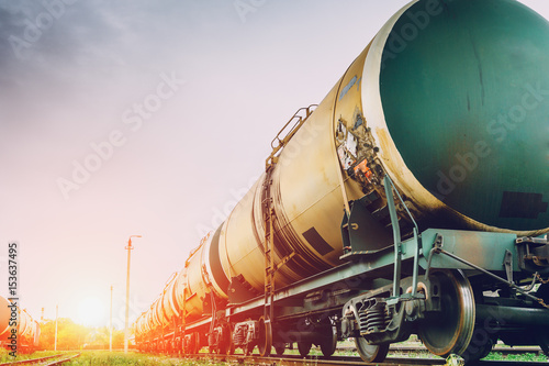Fototapeta Tanks with gas or oil transportation by railroad at sunset obraz