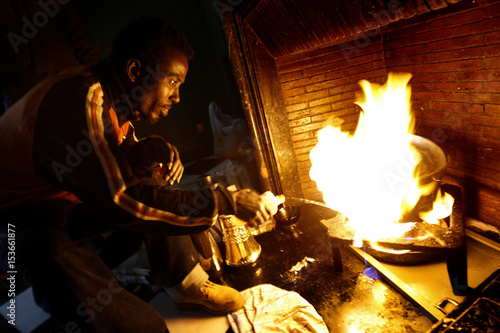 A Somalian refugee uses methylated spirits as he cooks