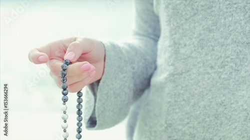 Fotografía  Woman, lit hand close up, counts Malas, strands of gemstones beads used for keeping count during mantra meditations