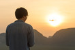 Young man flying drone and capture beautiful morning sunrise over scenic mountains view