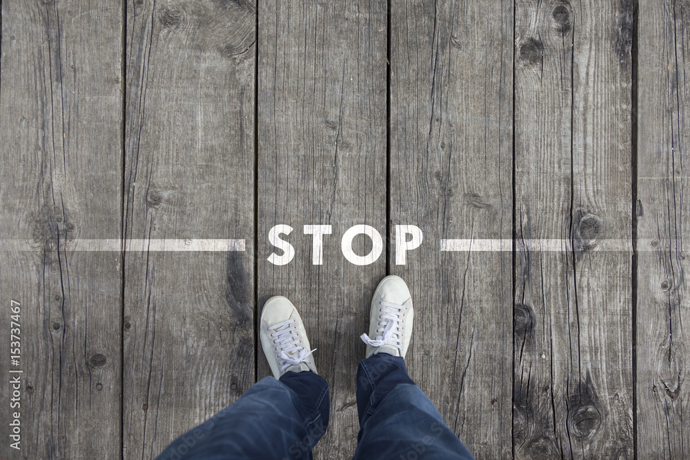 Fototapeta Man standing on the wooden boards with stop message on the floor, point of view perspective used.