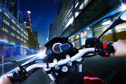 Fotografie, Obraz  Biker driving a motorcycle rides along the city street , night scene