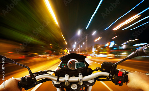Photo  Biker driving a motorcycle rides along the city street , night scene