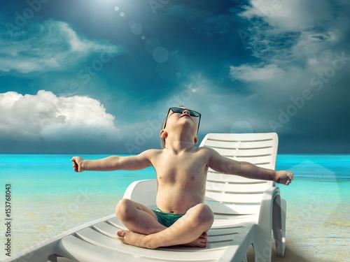 chlopiec-opalajacy-sie-na-lezaku-na-rajskiej-plazy