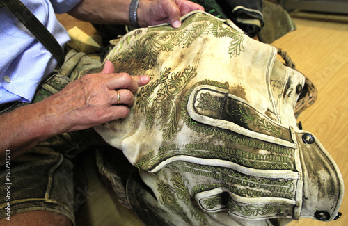A Customer Examines The Embroidery Of A Pair Of 80 Year Old Historic