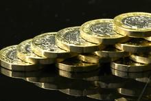 New British Pound Coins On A Black Background
