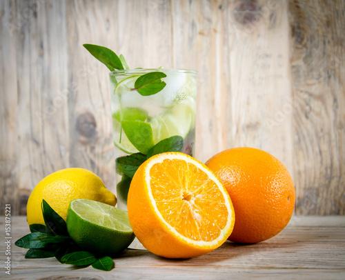 Poster Sap Fresh lemonade drink with ice. Fruit. Orange lemon lime and green mint leaves