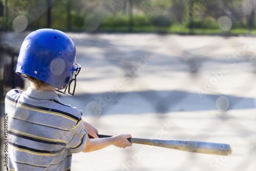 Young boy practicing hitting baseball at the batting cages Wallpaper Mural