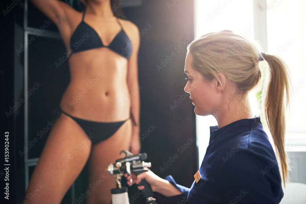 Fototapety, obrazy: Cosmetologist spraying tan bodypaint on woman in salon