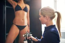 Cosmetologist Spraying Tan Bodypaint On Woman In Salon