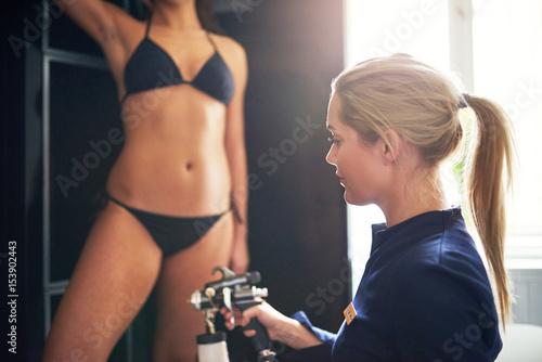 Cosmetologist spraying tan bodypaint on woman in salon Canvas Print