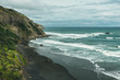 Volcanic beach with black sand and blue ocean