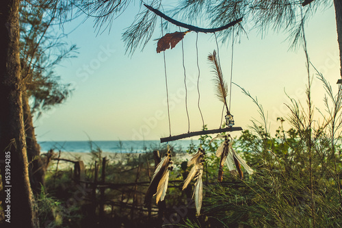 Amulet of sticks and feathers against the background of the ocean during sunset Wallpaper Mural