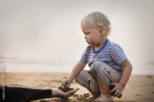 Little boy playing with sand on a beach