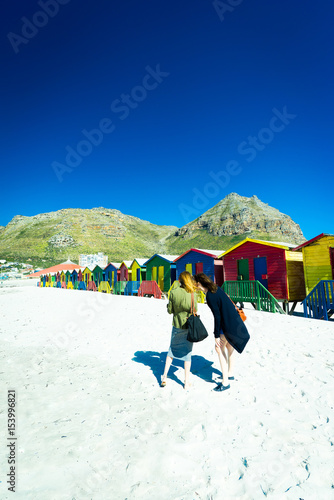 Foto op Canvas Zuid Afrika Two women taking pictures at Muizenberg beach, South Africa