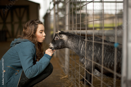 Teenage girl petting a goat.
