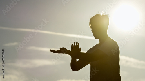 Silhouette male doing tai chi with the sun shining behind him