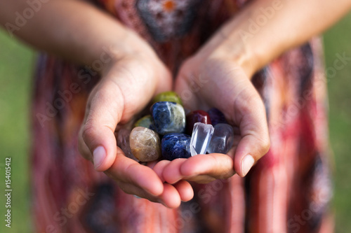 A young woman carefully holds a selection of vibrant gemstones as they reflect the soft sunlight.