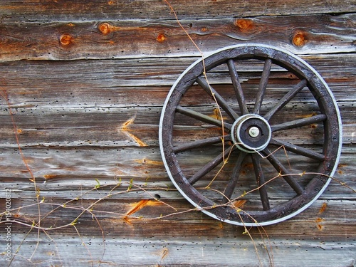 Photo  Old wooden wall with old wheel