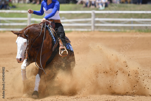 La pose en embrasure Equitation The front view of a rider in cowboy chaps and boots sliding the horse in the sand