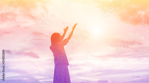 Fotografie, Obraz  Silhouette of woman praying over beautiful sky background