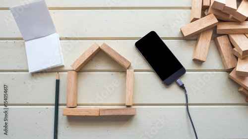 House Symbol Wooden Block And Smart Phone With Notebook And Pencil