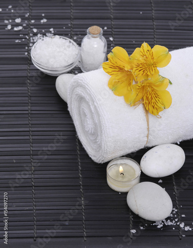 Poster Spa Spa setting with candle on towel ,stones on mat