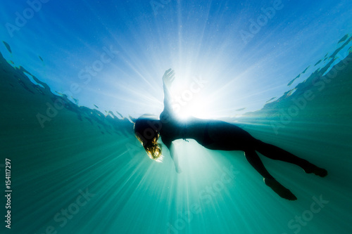 Fotografía  A beautiful woman floats on her back in the ocean as she is surrounded be bright ethereal light and sun rays