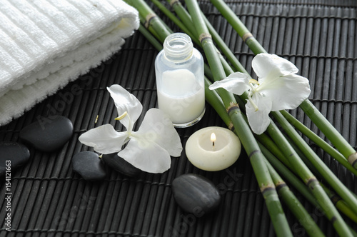 Poster Spa Spa setting with candle on towel ,stones ,grove on mat