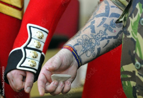 Guardsman Hughes of the Coldstream Guards puts on his tunic helped ...