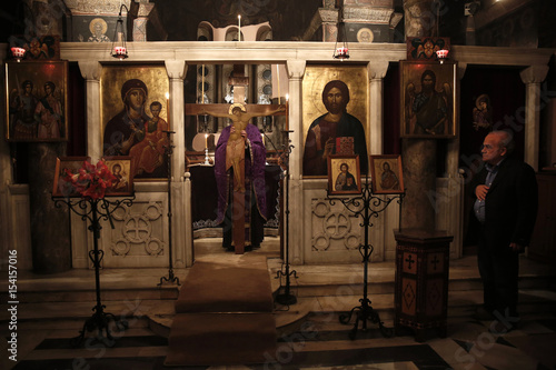 Orthodox priest carries crucifix during mass of Holy Thursday inside