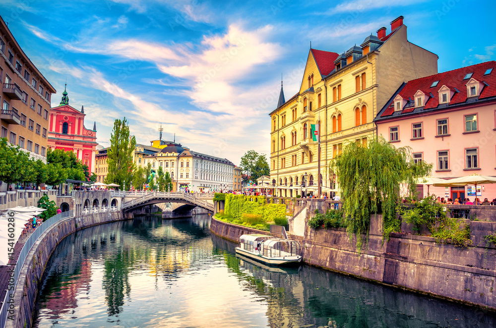 Fototapeta Cityscape view on Ljubljanica river canal in Ljubljana old town. Ljubljana is the capital of Slovenia and famous european tourist destination.