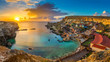 Il-Mellieha, Malta - Panoramic skyline view of the famous Popeye Village at Anchor Bay at sunset with traditional Luzzu boats, beautiful colorful clouds and sky