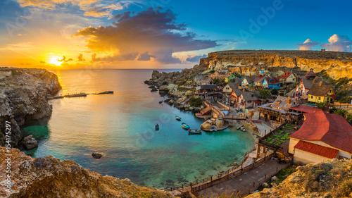 Obraz na płótnie Il-Mellieha, Malta - Panoramiczny widok na słynną Popeye Village w Anchor Bay o zachodzie słońca z tradycyjnymi łodziami Luzzu, pięknymi kolorowymi chmurami i niebem