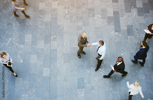 Adult office workers shaking hands in crowded hall