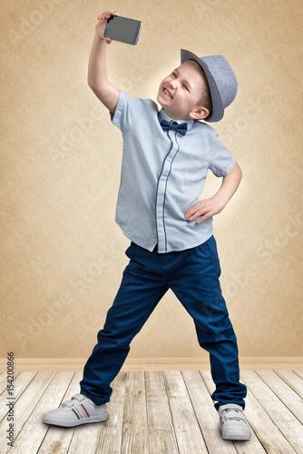 Photo sur Aluminium Akt Stylish boy in a hat making selfie on mobile phone, portrait.Kid's fashion.