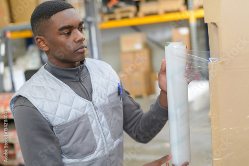 Photo  Young worker shrink wrapping pallet
