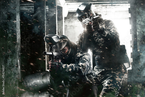 Fotografía  Two heavily armed masked paintball soldier on post apocalyptic background